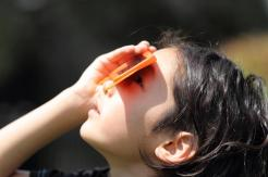 child-looking-through-orange-eclipse-glasses_web_1600x1067_color